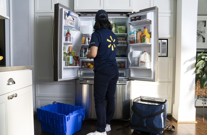 A woman wearing a Walmart employee uniform puts groceries inside a refrigerator at someone's home.