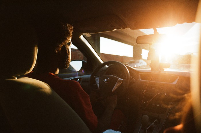 A person driving a car with sunlight streaming through the windshield.
