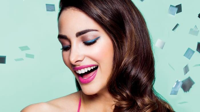 A smiling woman wearing makeup