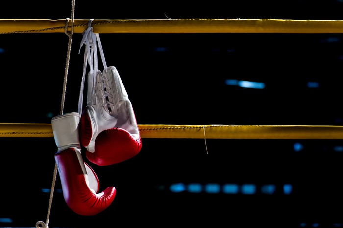 A pair of boxing gloves hanging on a rope that surrounds a boxing ring.