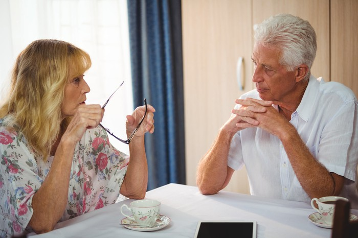 Older man and woman sitting at a table with teacups in front of them, sporting serious expressions.