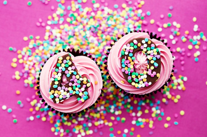 Two cupcakes, on a pink surface adorned with colorful sprinkles, with the number 40 written in sprinkles on top of them.