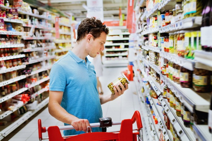 A man examining a jar of olives in the aisle of a grocery store