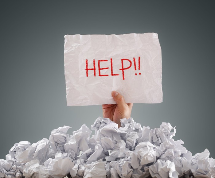 Person buried under pile of paper holding a sign that says HELP.