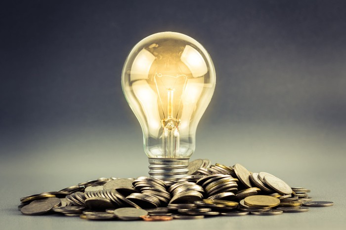 A lit up lightbulb resting on a pile of coins.