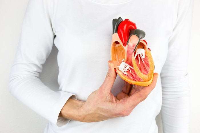 Man with half of a fake heart in front of his real heart