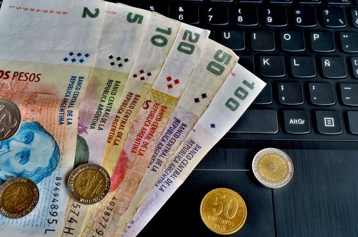 Argentine banknotes and coins on a keyboard.