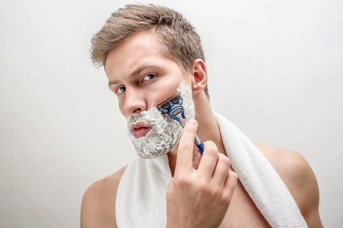 Man shaving with white towel around neck.