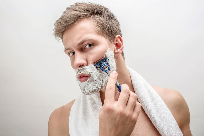 Man shaving with white towel around neck.