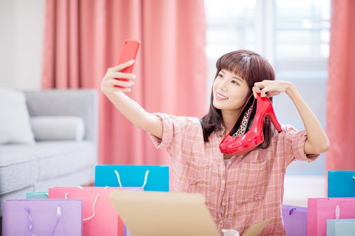 A smiling young woman takes a selfie with a pair of shoes.