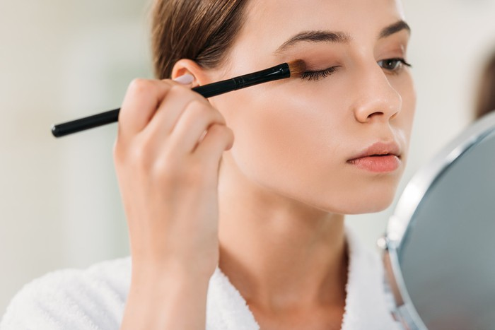 A woman applying eye makeup in front of a mirror.