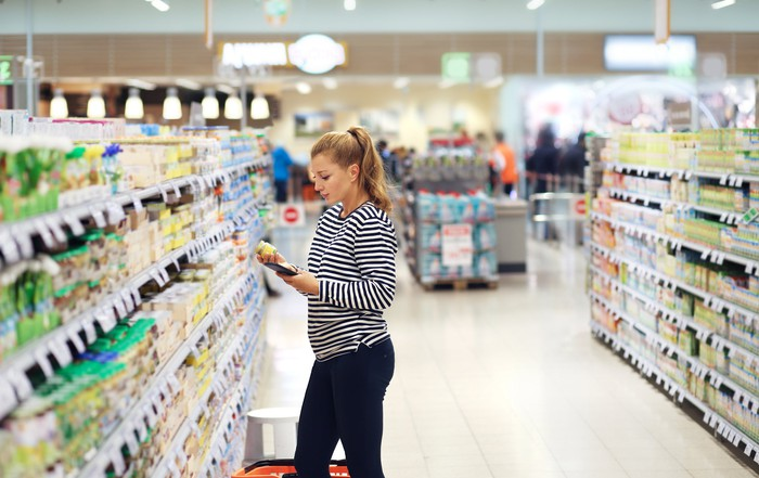 A young woman standing in a store aisle while looking at a grocery item in her hand.