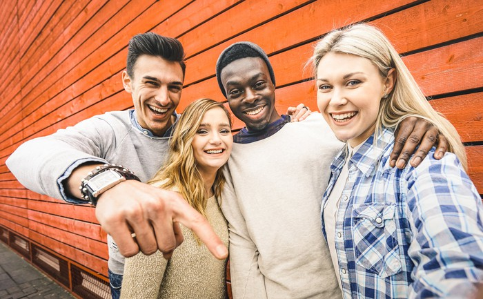 Four young people posing in front of a wooden wall.
