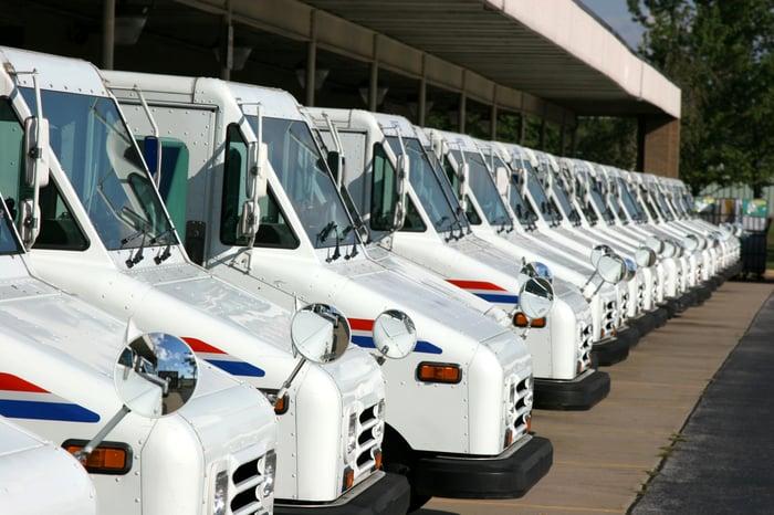 Long line of USPS post office trucks