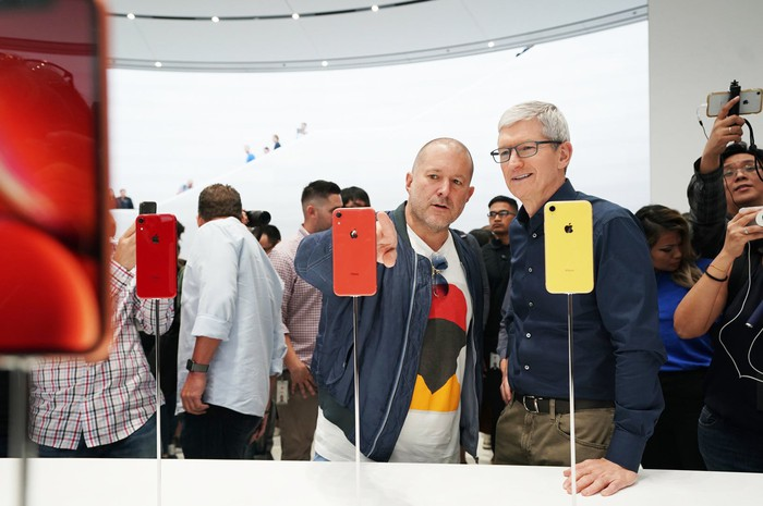 Jony Ive and Tim Cook looking at iPhones inside a crowded Apple Store.