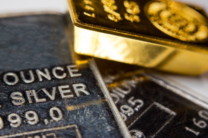Gold and silver ingots lying atop one another.