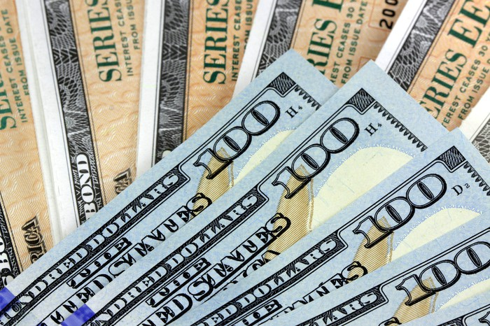 A fanned pile of cash bills lying atop a larger fanned pile of U.S. Treasury bonds.