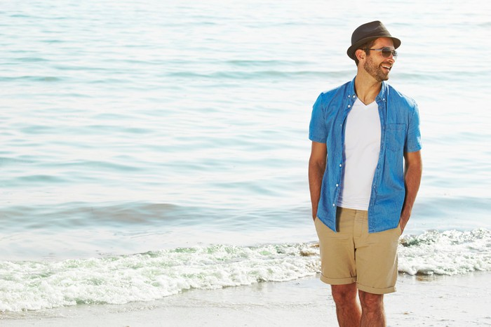 A young man in shorts, a chambray shirt, and hat walks and laughs on a beach.