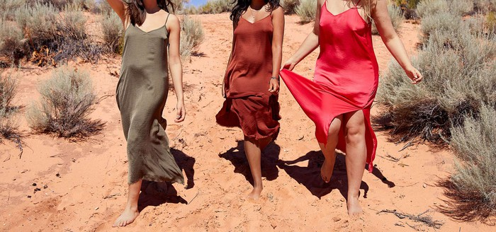 An Aerie ad: Three women wearing slip dresses and walking on sand.