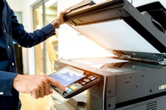 A businessman using a printer.