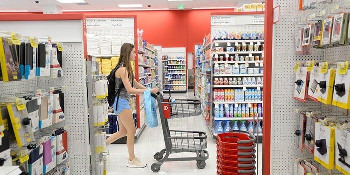 A girl pushing a shopping cart through a store