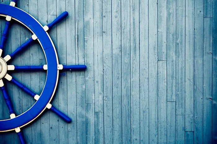 An antique boat helm wheel painted blue rests on a weathered wooden deck.