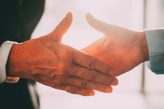 Closeup on a handshake between two businessmen, right before the two hands make contact.