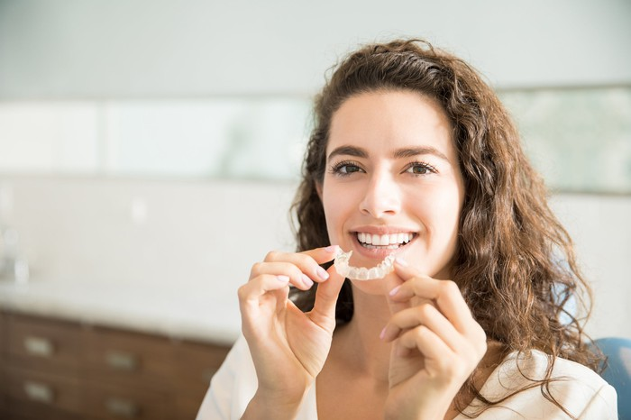 Smiling woman displays her orthodontic device.