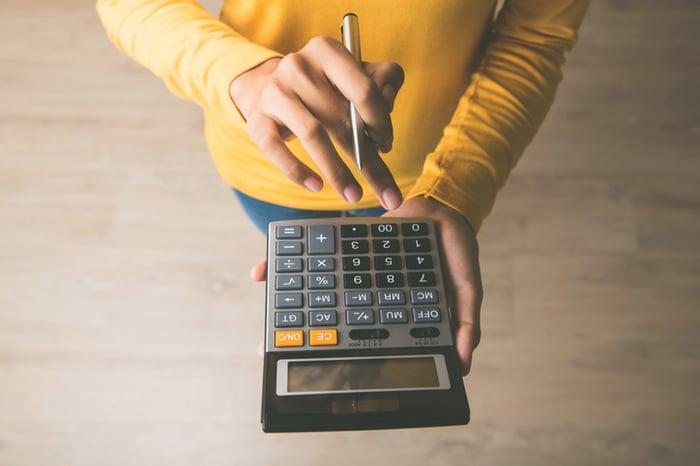 A woman holding a calculator.