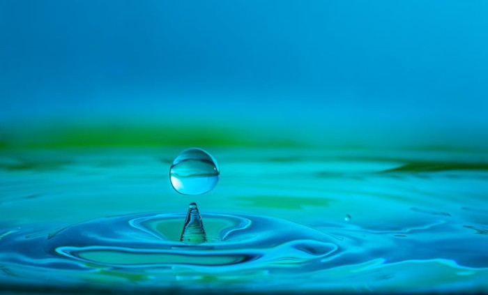Drop of water falling into a body of water causing ripples.