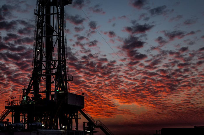 A drilling rig with red and orange clouds in the background.