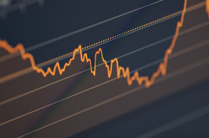 A blue stock chart with an orange line in a zigzag pattern.