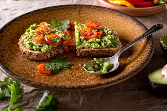 Avocado toast topped with sliced tomatoes in an attractive ochre porcelain bowl.