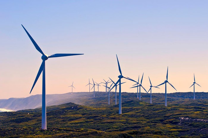 A row of wind turbines along a coast.
