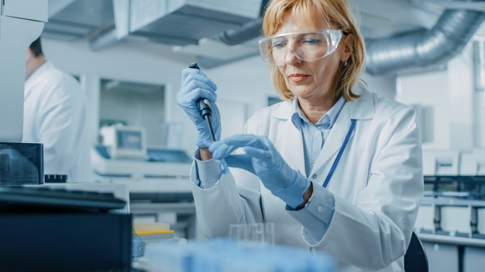 A woman in a lab coat and safety glasses uses a pipette in a lab.