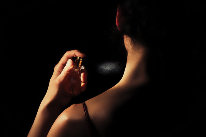 A woman spraying herself with perfume.
