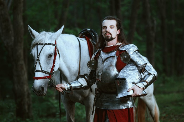 Knight in armor posing next to a white horse.