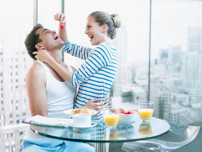 A couple sitting at a breakfast table in their apartment. The woman is feeding the man a strawberry.