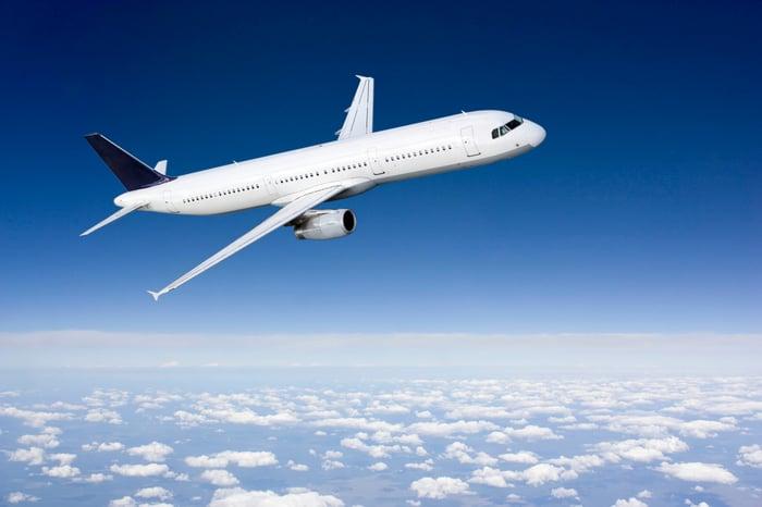 An airplane flies through blue skies.