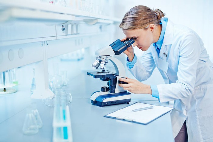 Young blond woman in a white lab coat using a microscope in a lab.
