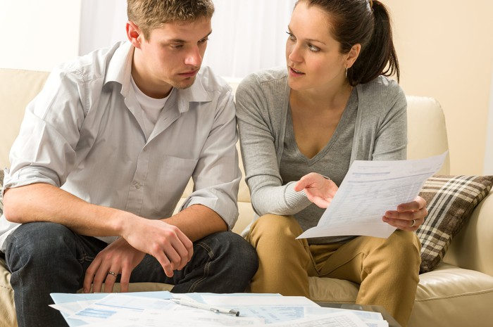 Couple sitting on a couch looking at financial paperwork in dismay.