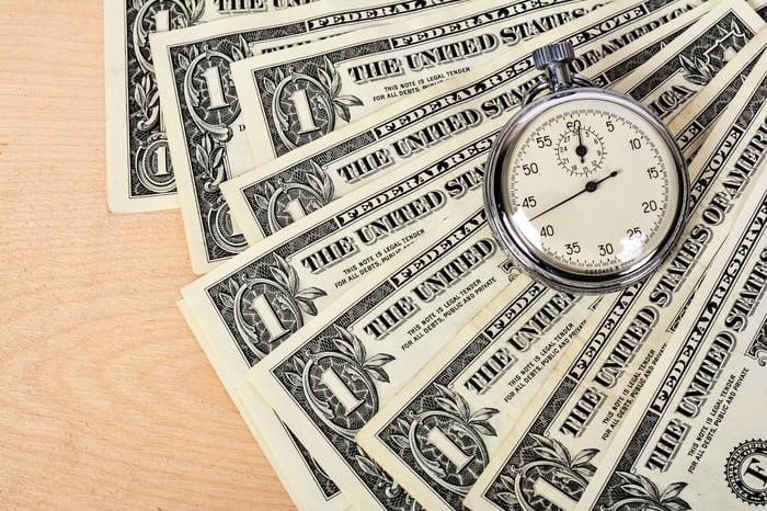 Dollar bills with timepiece.