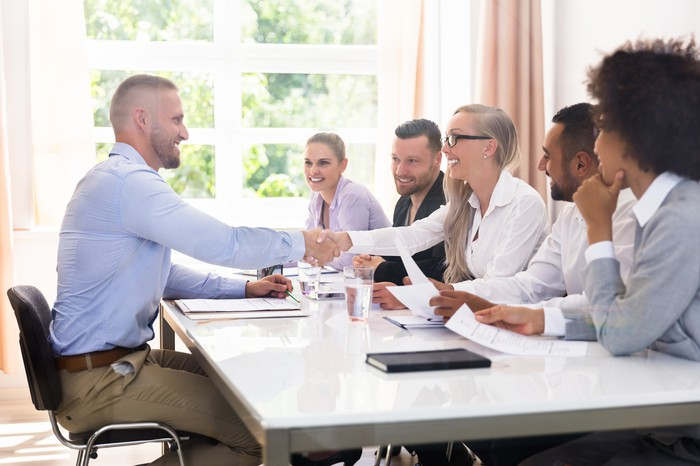 A male executive job candidate shakes hands with a female business team leader at a conference table as other employees look on.