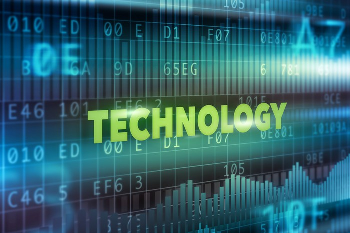 The word technology in green capital letters in front of a screen showing blue computer code.