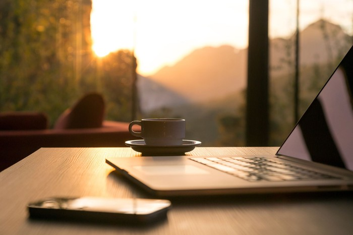 A laptop, smartphone, and cup of coffee sitting on a desk near a window overlooking a sunrise.