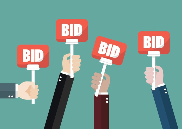 "Four hands hold up signs that say ""BID"" at an auction"