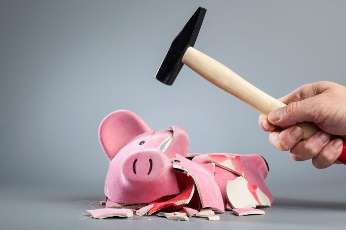 A man's hand holds a hammer above a broken piggy bank