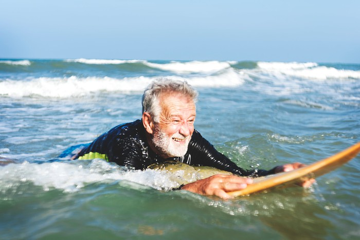 An older senior rides on his stomach on a surfboard in the ocean.