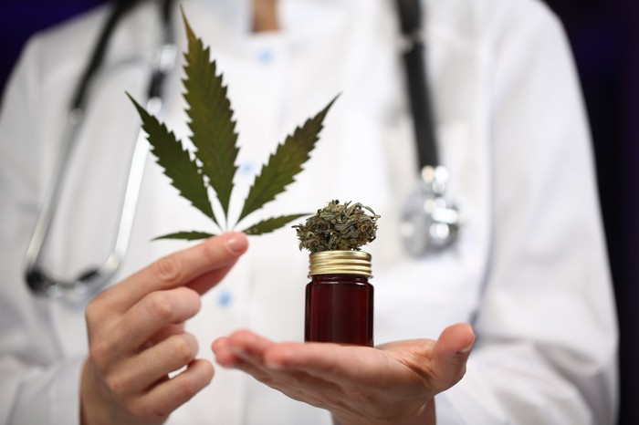 Person in lab coat and stethoscope holds a marijuana leaf and small jar of cannabis.