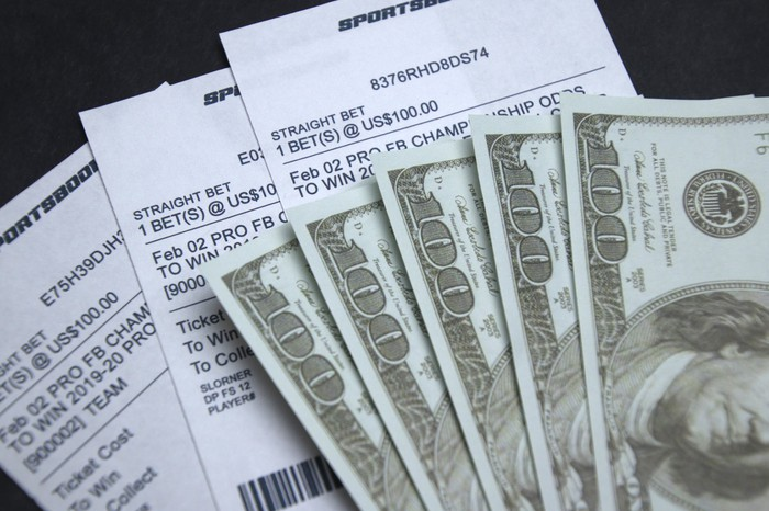 Sports betting tickets on a table with cash.